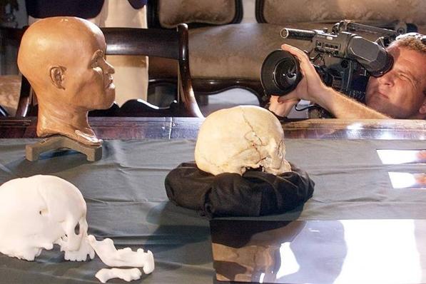 Foto de arquivo, de 1999, mostra homem filmando apresentação da reconstrução da cabeça de Luzia, fóssil humano mais antigo encontrado no BrasilAntonioScorza - 20.set.1999/AFP