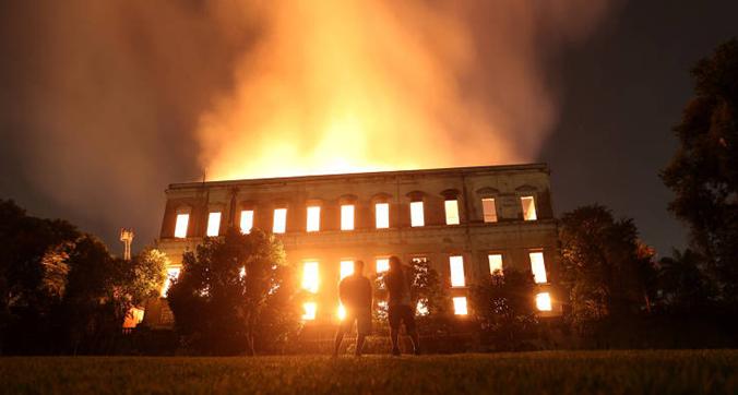 Pessoas observam incêndio q atingiu o Museu Nacional do Rio de Janeiro, um dos mais antigos do Brasil, na noite deste domingo (2) Ricardo Moraes /Reuters
